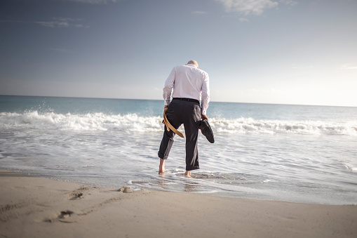 Retired businessman carrying shoes and tie, paddling in sea